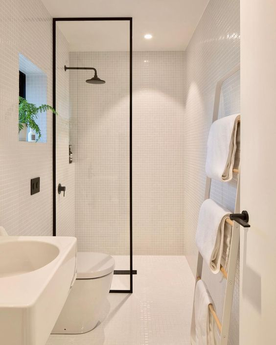 a small white minimalist bathroom clad with tiny tiles, with a ladder for towels, white appliances and a shower with a glass partition