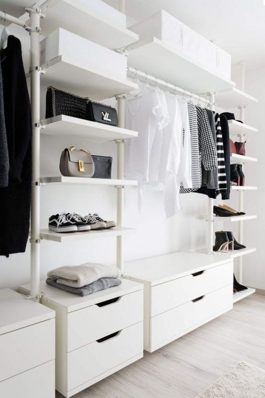 a stylish and simple white closet with open shelves, dressers and boxes overhead for storage is a cool minimalist idea