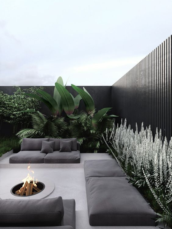 a stylish and ultra-minimalist terrace in neutrals, with black cushions and pillows, a fire pit, greenery and large plants is a very chic space