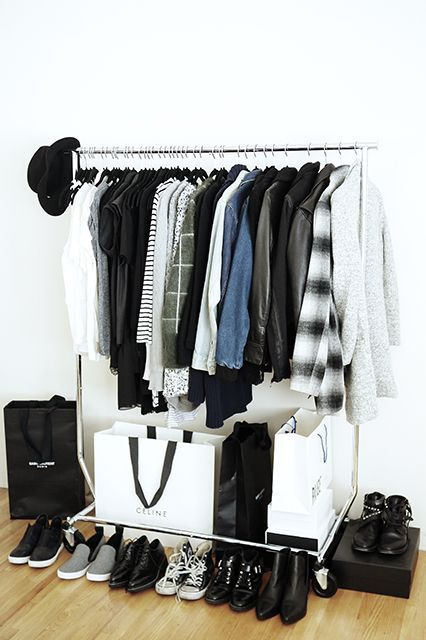 a stylish makeshift closet with shoes stored around and some bags used for storage, too