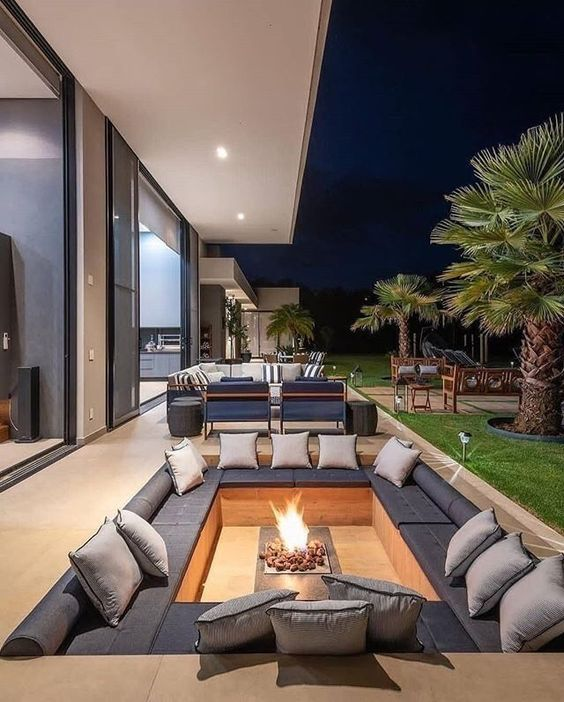 a stylish minimalist sunken fire pit with a built-in bench, lots of cushions and pillows and a fire pit in the center is a very chic idea