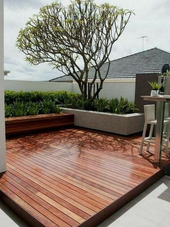 a stylish minimalist rich-stained deck with a built-in bench, potted greenery and a tree, a metal and wood tall table and tall stools
