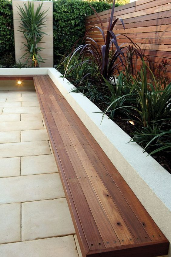 a stylish minimalist terrace with stone tiles, a built-in floating bench, various greenery growing and built-in lights is a cool idea