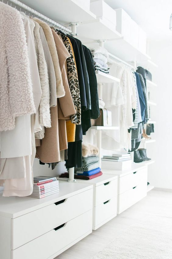 a stylish white minimalist closet with dressers, open shelves and holders for clothes hangers plus white boxes