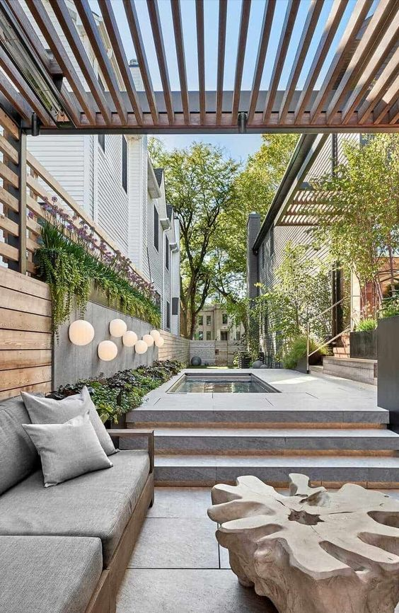 a super stylish minimalist terrace clad with stone tiles, with a pool, a wooden sofa with grey upholstery and a coffee table of piece of wood