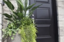 a tall concrete faceted planter with plenty of greenery is a gorgeous solution for a modern space