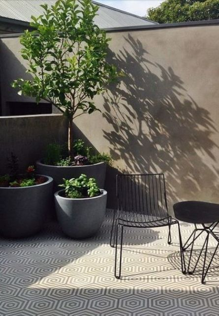 a tiny minimalist terrace with geo tiles, concrete planters with greenery and trees, a black table and a black chair