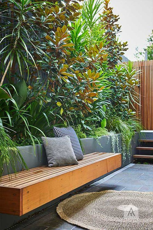 a very simple and minimalist terrace clad with concrete tiles, with concrete tall planters for greenery and bushes, a floating bench and a small ladder