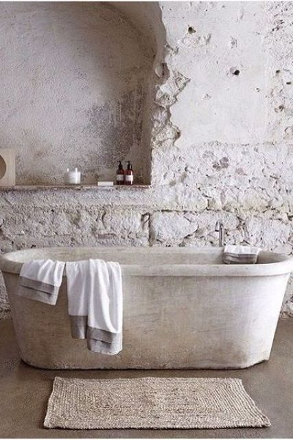 a wabi-sabi bathroom in neutrals with stone wall, a stone tub and a jute rug looks very roough and imperfect