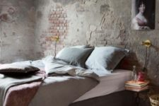 a wabi-sabi bedroom with a rough brick wall, a concrete floor and some cozy furniture to soften the space