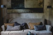 a wabi-sabi interior with a rough wooden wall, a wooden wall art of rough elements and a coarse textile sofa
