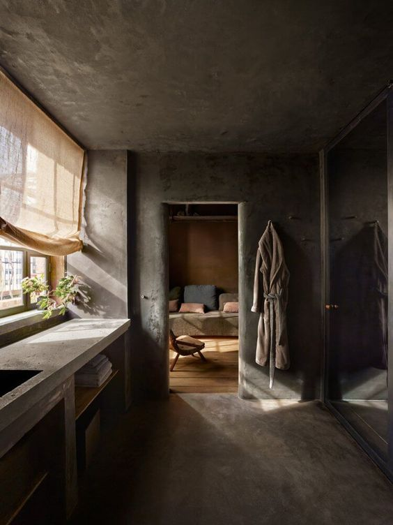 a wabi-sabi kitchen fully done in concrete, with a countertop and a curtain for a softer touch