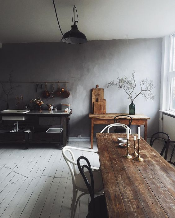 a wabi sabi kitchen with a white plank floor, stained wooden furniture and a metal kitchen island with sinks