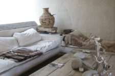 a wabi-sabi living room with brutal wooden furniture, vases, stones and concrete walls