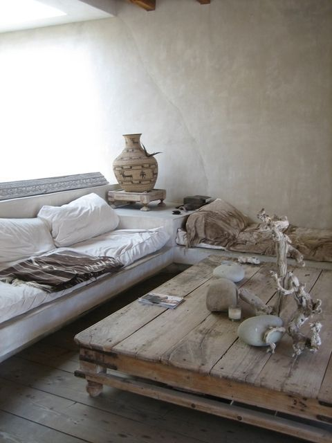 a wabi-sabi living room with brutal wooden furniture, vases, stones and concrete walls