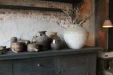 a wabi-sabi space with a rough brick wlal, a wooden cabinet, some rough stone vases and planters