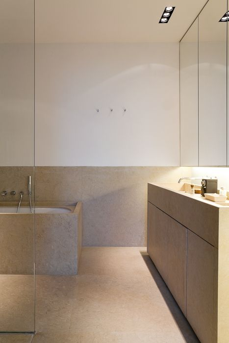 a warm-colored minimalist bathroom clad with tan-colored stone, a large vanity, a mirrored storage cabinet and a stone clad tub