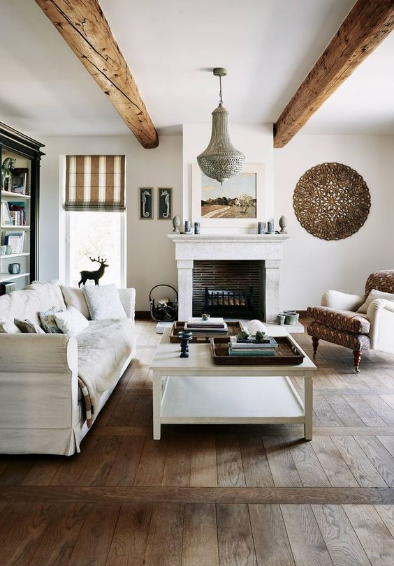 a welcoming Provence living room with a fireplace, neutral furniture, wooden beams and a low coffee table plus a bookcase
