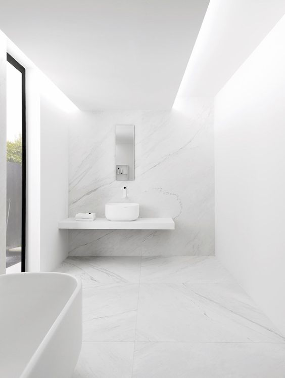 a white minimalist bathroom with a large window, a floating vanity, a bowl sink and a bathtub plus white marble