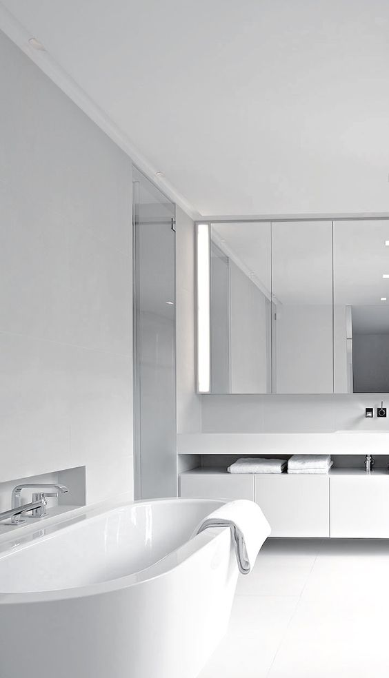 a white minimalist bathroom with a mirrored cabinet, a floating vanity, a white tub, stainless steel fixtures