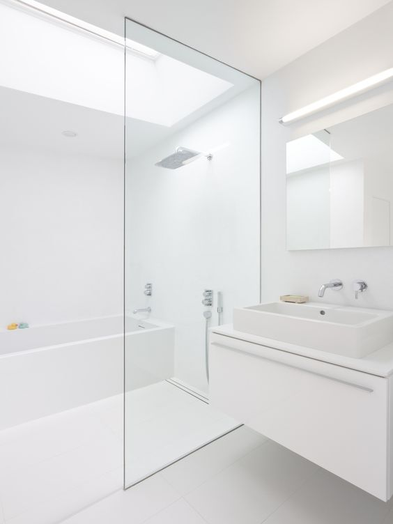 a white minimalist bathroom with a skylight, a white floating vanity, white appliances and built-in lights