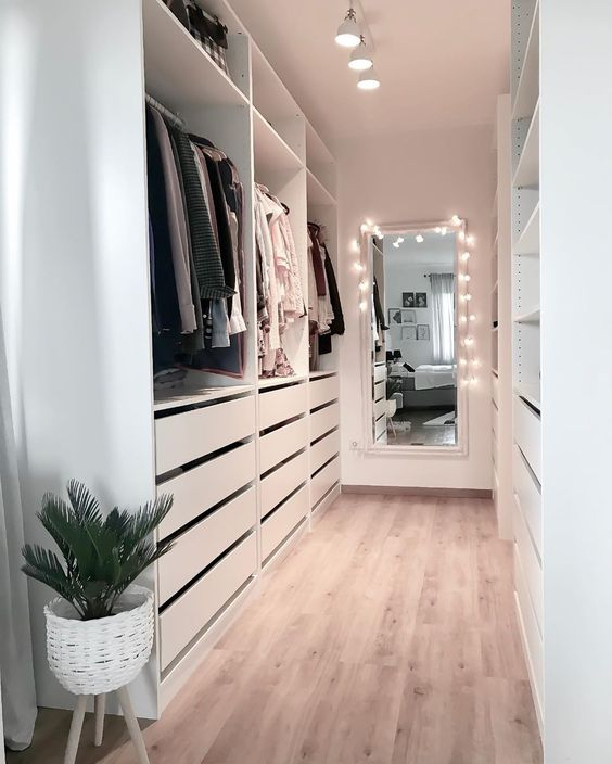 a white minimalist closet with drawers, open shelving and holders plus a mirror with lights to see what to wear