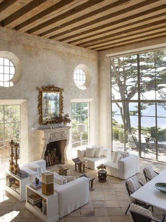 an airy and serene Provence living room with a fireplace, neutral furniture, wooden beams, bookshelves and a dining space