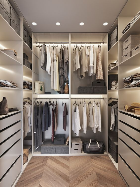 an ivory minimalist closet with built-in lights, drawers, open shelves and open holders for hangers