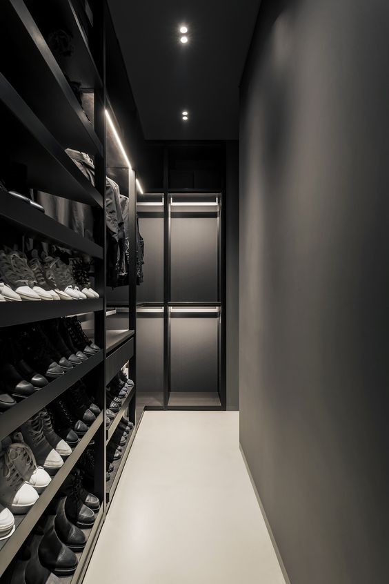 an ultra-minimalist black and graphite grey closet with lots of shoe shelves and some drawers plus holders for hangers