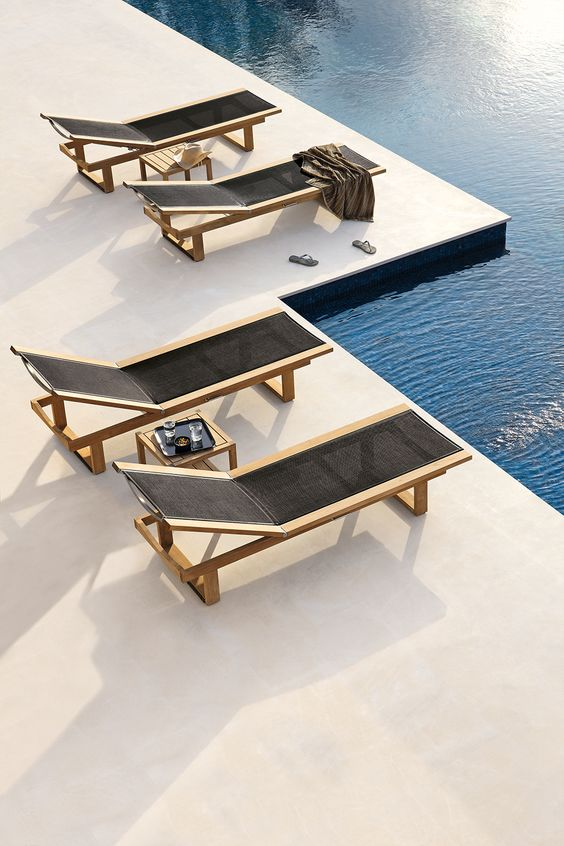minimalist light-colored wood loungers with black fabric are a nice match for a minimalist outdoor space