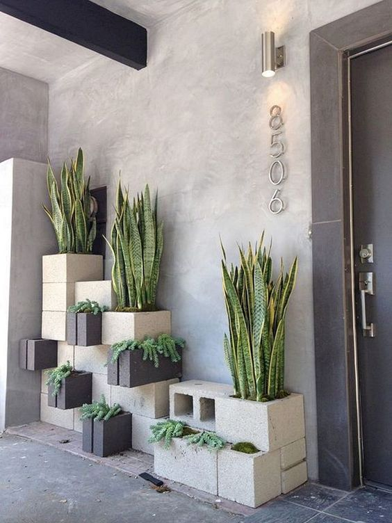 stylish stacked concrete planters in grey and black with various kinds of plants will totally change your outdoor space