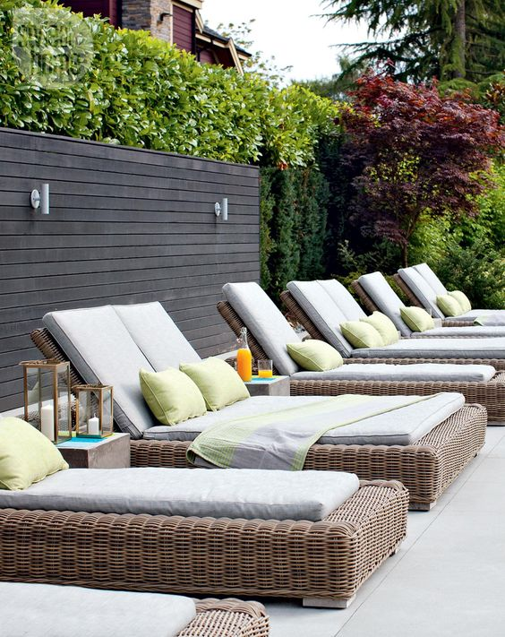 wicker loungers with white upholstery and colroful pillows are a classic and cool solutions for outdoors