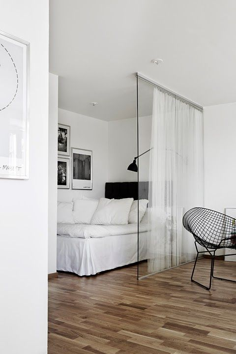 a Nordic bedroom with a bed and some black and white artworks separated from the rest of the apartment with a glass sliding door