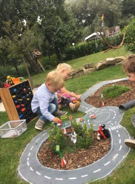 a backyard play area with race tracks will attract both girls and boys and you may add some plants and blooms there