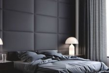 a black padded fabric statement wall perfectly fits a moody contemporayr bedroom with a masculine feel