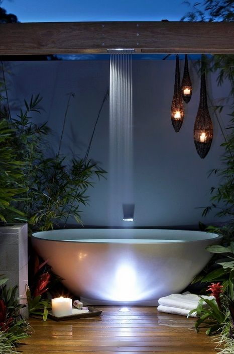 a chic contemporary space with an oval tub, a waterfall shower, some drop-shaped candle lanterns and greenery around
