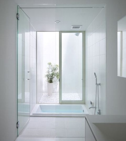 a clean white bathroom with a sunken bathtub, a skylight, potted greenery and a sink is very minimal and simple