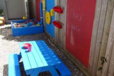 a colorful play area with a bright blue sand box, some plastic decor on the fence and a bright blue dining set