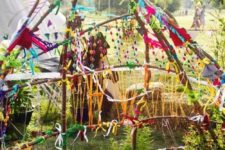 a colorful teepee covered with yarn, pompoms, buntings, flags and other bright stuff plus potted greenery