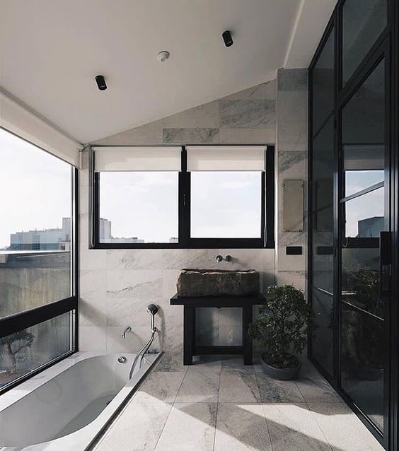 a contemporary bathroom in black and neutrals, with a rough stone sink, a sunken bathtub with a gorgeous panoramic view