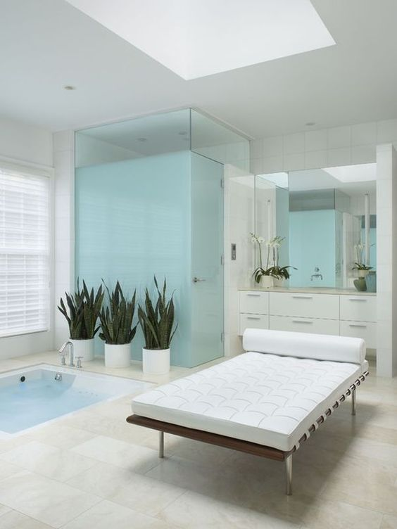 a contemporary bathroom in white and light blue, with a sunken bathtub and a leather couch plus potted plants for an outdoorsy feel