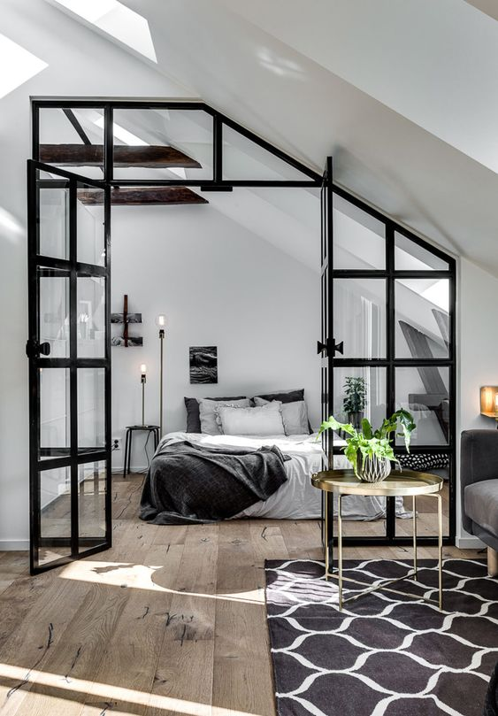 a cozy Nordic bedroom with a bed, nightstands, skylights, table lamps and a glass wall with a door to connect it to the rest of the space