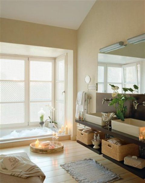 a cozy and neutral bathroom with a sunken bathtub, a wooden floor, blooms and candles in trays plus a large mirror