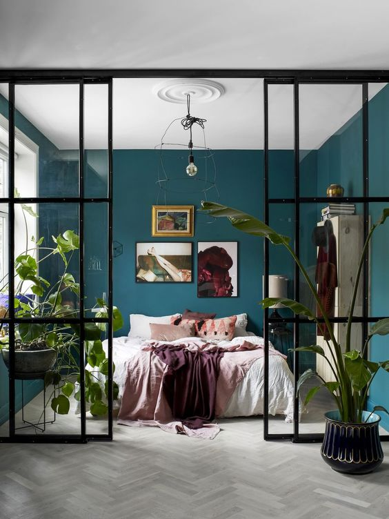 a cozy bedroom with a bed, a vintage storage unit and some bold art, with hunter green walls and a glass wall with doors