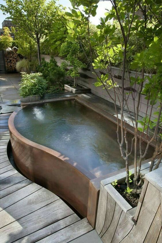 a curved plunge pool with potted and planted greenery around will refresh you very well on a hot day