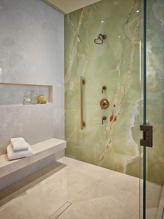 a fantastic shower space in neutrals accented with a green onxy statement wall that really wows