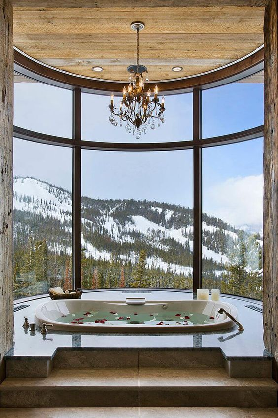 a gorgeous bathroom with a panoramic view, a sunken bathtub, a chandelier, candles is a fantastic space to enjoy your bath time