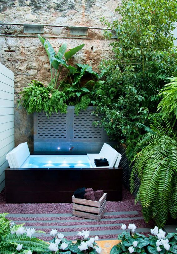 a jacuzzi, lush greenery around it, a crate with towels and some blooms for a welcoming space