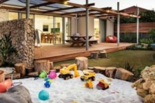 a large sand box with tree stumps and stones around looks very natural and bright with fun toys