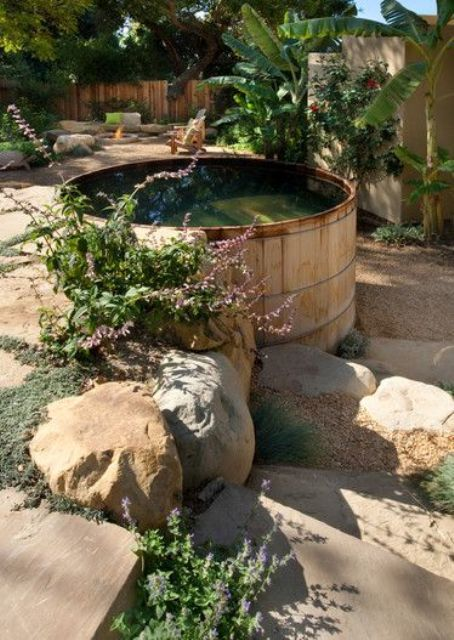 a large wooden tank is used as a plunge pool and looks very natural in rocks, greenery and blooms growing around